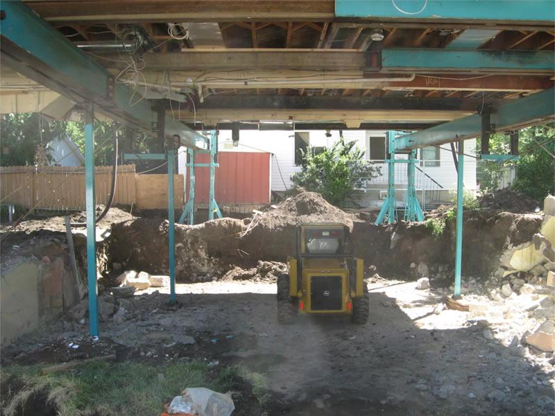 Skid Steer grading soil in preparation for basement construction
